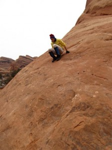 Bob crab-walking down steep rock in Arches